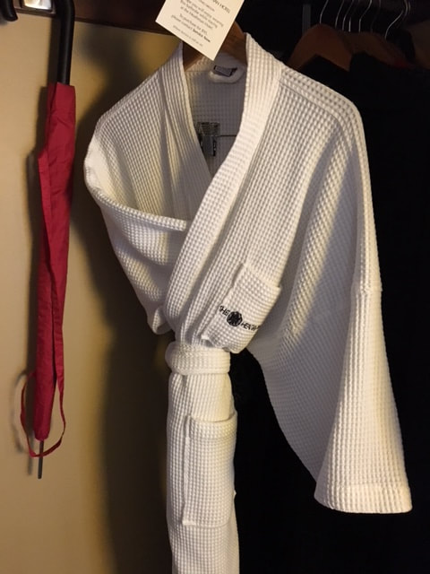 folded bath robe hanging from coat hanger in a closet