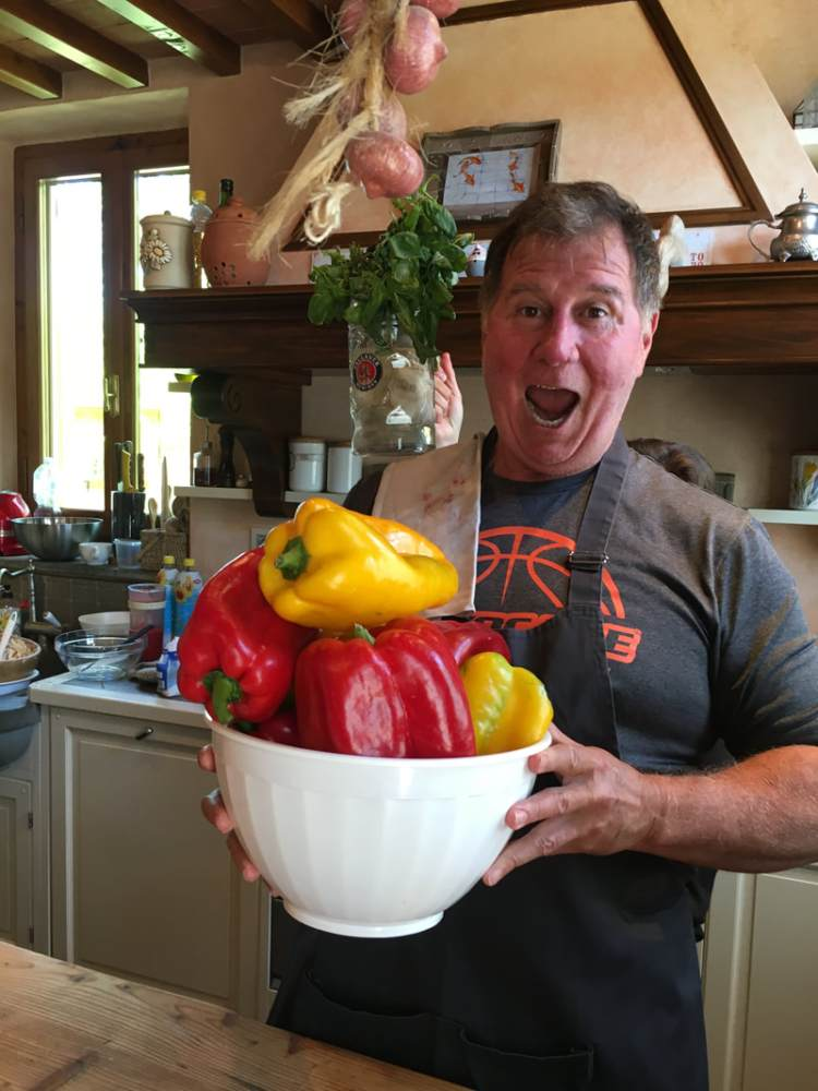 man holding a bowl of very large peppers
