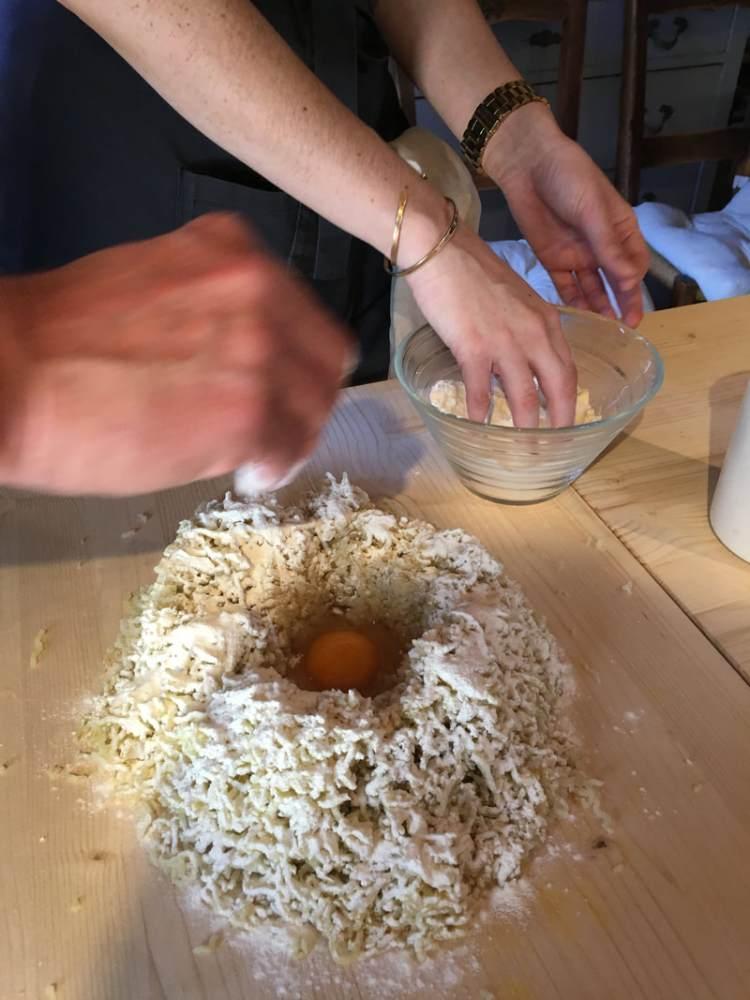 people's hands mixing potato gnocchi