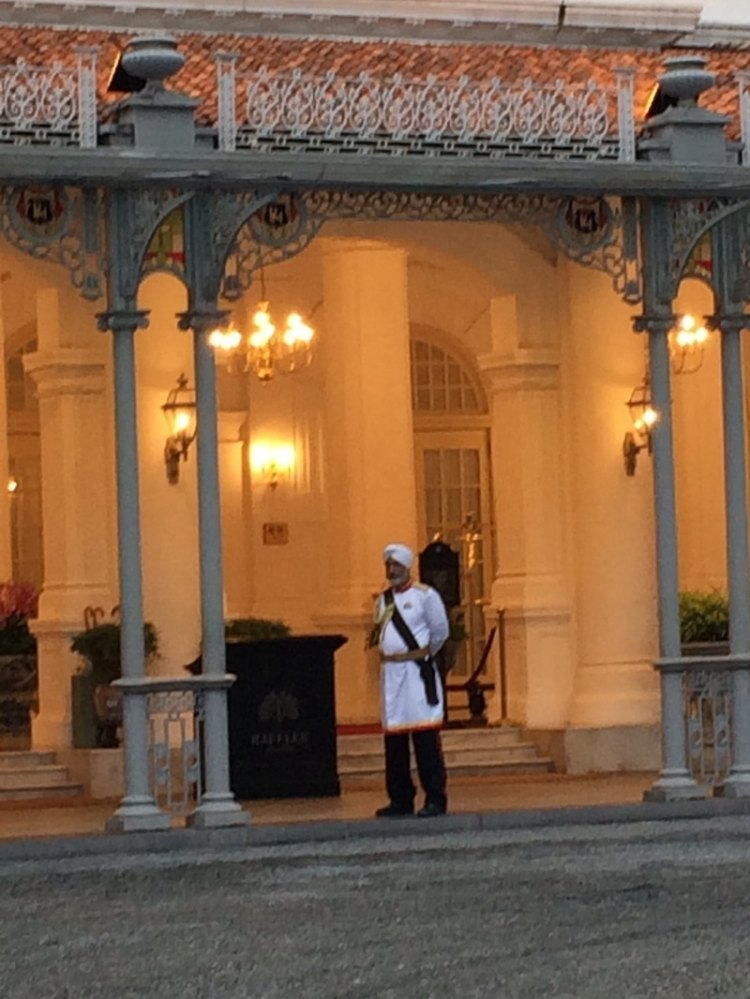 bellman standing in front of The Raffles Hotel in Singapore